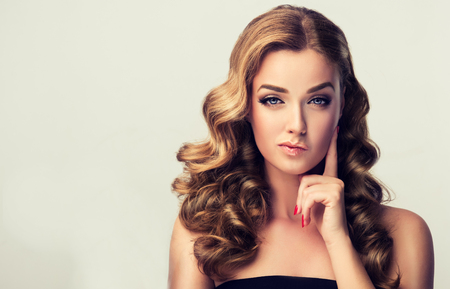 Photo pour Expression of worry and suspiciousness on face of perfectly looked, young, beautiful woman. Pin-up style make up, and red manicure. - image libre de droit