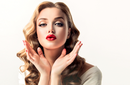 Foto de Beautiful woman  looks like a star of a retro movies . Vintage pin-up   girl  is sending air  kiss . Model with  curly hair and  bright makeup. - Imagen libre de derechos