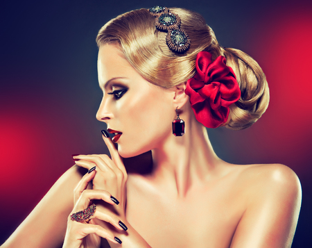 Photo for Retro style hairstyle,smokey eyeshadow and bright red lipstick on the face of young model. Elegant gesture of hands decorated by jewelry rings and black manicure. - Royalty Free Image