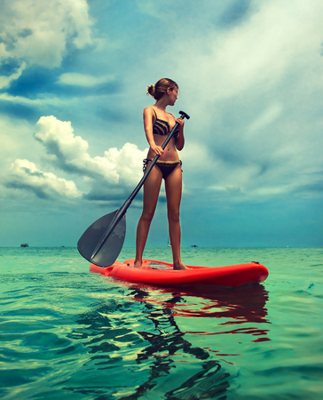 Foto de Young slender woman dressed in a bikini swimsuit is sailing on the board ruling by paddle. Example of entertainment on the sea, active lifestyle and water sport. - Imagen libre de derechos