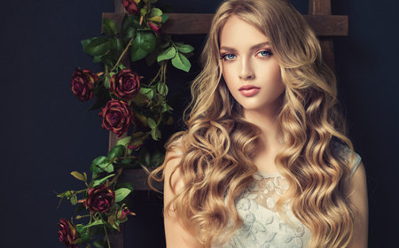 Photo pour Young, blonde haired beautiful model with long, wavy,well groomed hair. Stylish, loose hairstyle with freely lying curls. - image libre de droit