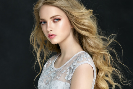 Photo pour Young, blond haired woman  with voluminous hair. Beautiful model with stylish, loose hairstyle with freely lying curls.and vivid make-up.Flying hair. - image libre de droit