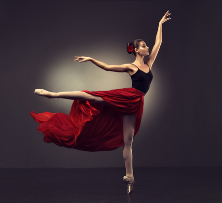Photo pour Ballerina. Young graceful woman ballet dancer, dressed in professional outfit, shoes and red weightless skirt is demonstrating dancing skill. Beauty of classic ballet. - image libre de droit