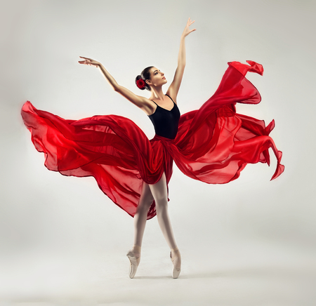 Foto de Ballerina. Young graceful woman ballet dancer, dressed in professional outfit, shoes and red weightless skirt is demonstrating dancing skill. Beauty of classic ballet. - Imagen libre de derechos
