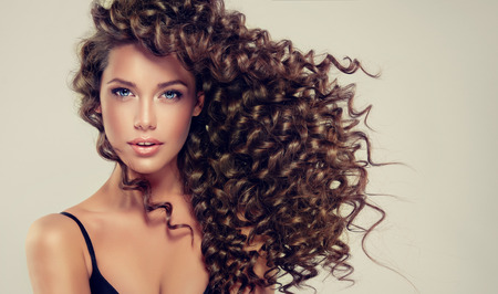 Foto de Young, brown haired beautiful model with long, wavy,well groomed hair.Tensed, spring-like curls on the hair. - Imagen libre de derechos
