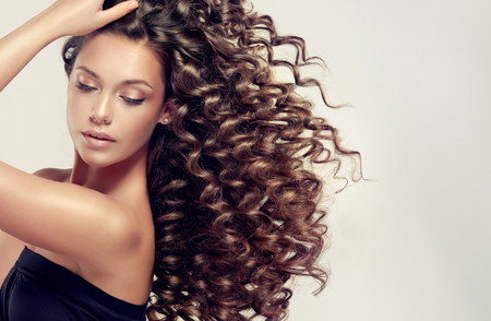 Foto de Tensed, spring-like curls on the hair.Incredibly dense, wavy,and shiny hair. - Imagen libre de derechos