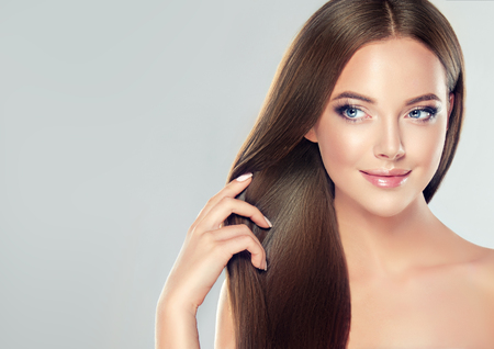 Photo pour Young, brown haired beautiful model with long,  straight, well groomed hair is touching own hair with tenderness. - image libre de droit