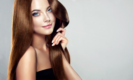 Photo pour Young, brown haired woman  with voluminous hair.Beautiful model with long, dense, straight hairstyle and vivid makeup, is touching own hair with tenderness. Symbol of attentiveness to hair and good care of it. - image libre de droit