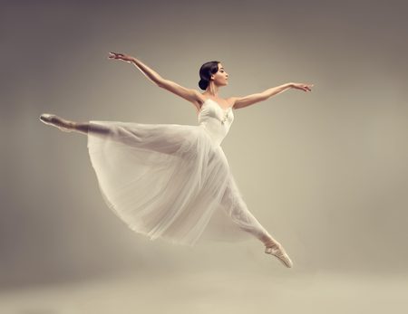 Photo pour Ballerina. Young graceful woman ballet dancer, dressed in classic, white Chopin tutu, and professional ballet shoes  is demonstrating dancing skill. Beauty of classic ballet. - image libre de droit