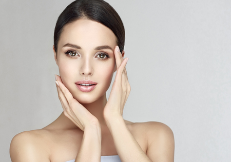 Foto de Gorgeous, young, brown haired woman with clean fresh skin is touching the face.  Light smile on the perfect face. Facial treatment, cosmetology, beauty technologies and spa. - Imagen libre de derechos