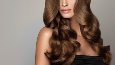 Foto de Young, brown haired woman  with voluminous hair. Beautiful model with long, dense and curly hairstyle and vivid make-up. Perfect hair. Incredibly dense, wavy,and shiny hair. - Imagen libre de derechos