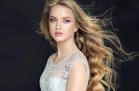 Photo for Young, blonde haired beautiful model with long, wavy,well groomed hair. Flying hair. - Royalty Free Image