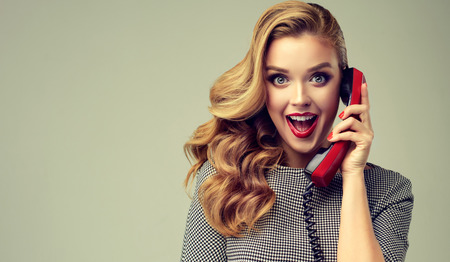 Photo for Blonde haired young woman with pin-up style makeup and hairstyle, is speaking by vintage phone. Extremely surprised and happy facial expression. - Royalty Free Image