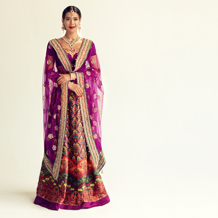 Photo for Young attractive woman, dressed in a traditional indian suit-sari. Splendid jewelry set, purple blouse and shawl (dupatta) with gilded hand-made decoration. Portrait in a full height. - Royalty Free Image
