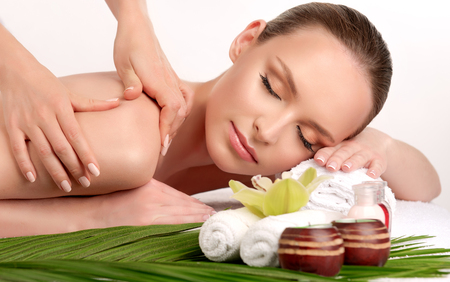 Photo pour Young lady is laying on massage table and gets massage treatment.Spa and body massage.Tender and soft hands of massage specialist is making massage on the back of young and appealing woman. Beauty and Spa treatment concept. - image libre de droit