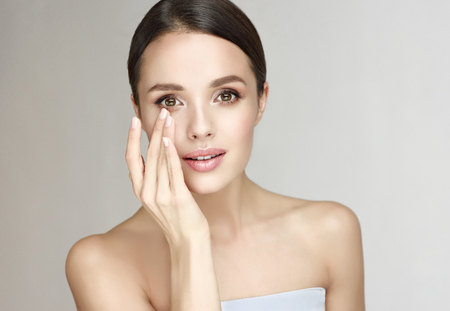 Photo pour Gorgeous, young, brown haired woman with clean fresh skin is rubbing ointment in a round eyes area. Facial treatment, cosmetology, beauty technologies and spa. - image libre de droit