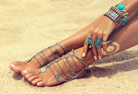 Foto de Womans hands and legs covered by bracelets and rings in a Boho style.Woman is sitting in relaxed position on tropical sandy beach. Body parts . - Imagen libre de derechos