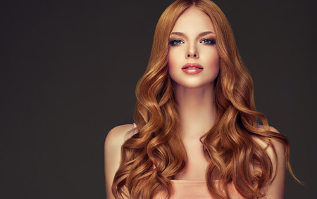 Foto de Young, red haired woman  with curly and voluminous hair. Beautiful model with long, dense wavy hairstyle and vivid make-up. Perfect hair waves and passionate look. - Imagen libre de derechos