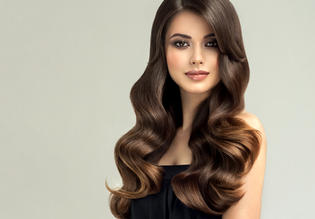 Photo pour Young, brown haired woman  with curly and voluminous hair. Beautiful model with long, dense wavy hairstyle and vivid make-up. Perfect hair waves and sexy look.Incredibly undulating and shiny hair. - image libre de droit
