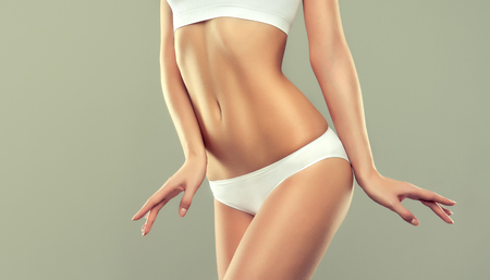 Photo for Perfect woman's body is dressed in a white sport underwear. Well posing model is demonstrating elegant gesture and healthy, graceful figure. An example of slender body shapes for fitness and esthetic cosmetology. - Royalty Free Image