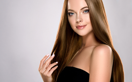 Foto de Young, brown haired woman  with voluminous hair.Beautiful model with long, dense, straight hairstyle and vivid makeup, is touching own hair with tenderness. - Imagen libre de derechos