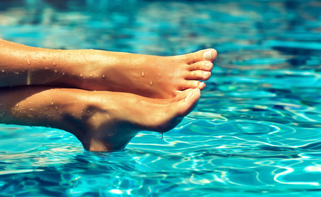 Photo pour Tanned, well-groomed crossed woman's feet, covered by drops of clean water is resting above blue, moving surface of waterpool.Pedicure, feet care and Spa. - image libre de droit