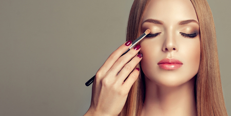 Photo for Professional makeup artist is coloring eyelids of perfectly looking young model. Double-colored, gilded eyelids and rose lipstick. Makeup in progress. Fashion, makeup and cosmetic. - Royalty Free Image