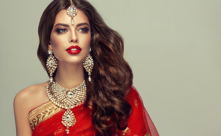 Photo for Young attractive woman, covered by traditional indian red shawl (dupatta) and dressed in hand-made kundan style jewelry set. Posh jewelry set is consisting of big earrings, bright necklace and head adornment (tikka). Perfect, dense, wavy, freely flying hair and smoky eyes style makeup. - Royalty Free Image