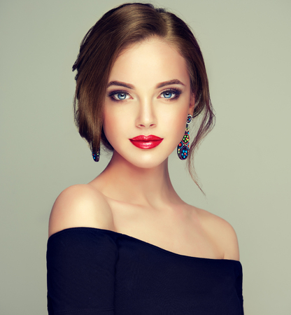 Foto de Portrait of young, brown haired beautiful woman with long, well groomed hair gathered in elegant evening hairstyle. Hairdressing art, hair care and beauty products. - Imagen libre de derechos