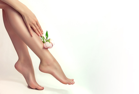 Foto de Perfect, graceful woman hand with light pink manicure on the nails  is holding flower of peony and touching well-groomed feet.  Spa, scrub, depilation and foot care. - Imagen libre de derechos