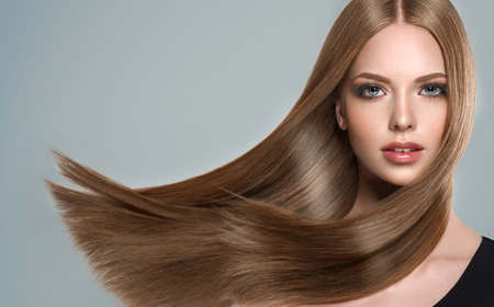 Photo pour Young, brown haired woman  with straight and voluminous hair. Beautiful model with long, dense straight hairstyle and vivid make-up. Perfect flying hair and sexy look. - image libre de droit