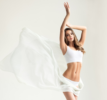 Photo pour Young alluring woman with graceful and slim body dressed in a white sport underwear and partially covered by tender, silk textile. Slender female figure, as a symbol of health and harmony. - image libre de droit
