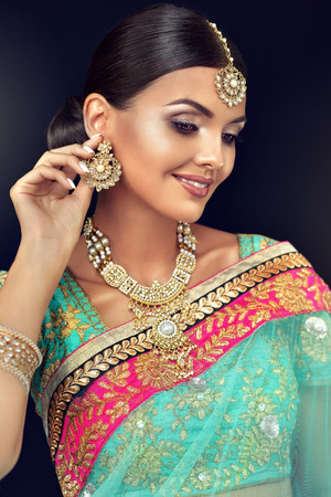 Photo for Young attractive woman, dressed in a traditional indian suit-sari, with green blouse and shawl (dupatta) with gilded hand-made decoration. Posh jewelry set is consisting of big earrings, bright necklace, head adornment (tikka) and gold nose ring. - Royalty Free Image