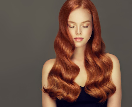 Foto de Young, red haired beautiful model with long,  curly, well groomed hair. Irish beauty. Excellent hair waves. Hairdressing art and hair care. - Imagen libre de derechos