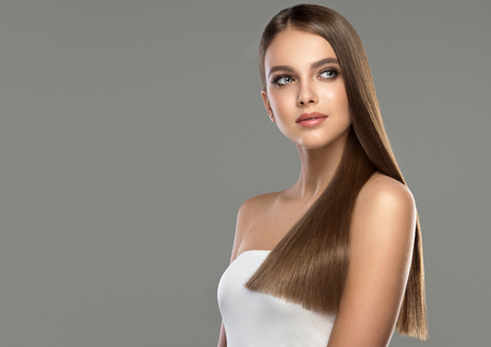 Photo pour Young and pretty woman with soft smile on the face in demonstrating perfectly looking, dense and straight shiny hair. Natural gloss of healthy hair. Hair care and hairdressing art. - image libre de droit
