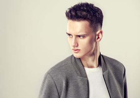 Photo pour Portrait of attractive mature man dressed in a white t-shirt and grey stylish bomber jacket. Fashionable haircut with the short temples on the head of young handsome male-model. Example of trendy man hairstyle. Hairdressing art. - image libre de droit