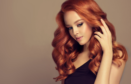 Photo pour Young, red haired woman is touching tenderly own perfect red hair. Beautiful model with long, dense, curly hairstyle and vivid makeup. Hairdressing art and hair care. - image libre de droit