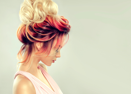 Foto de Young attractive woman is demonstrating multi colored hair gathered in elegant evening or wedding hairstyle. Hairdressing art and coloration of hair. Portrait in profile. - Imagen libre de derechos