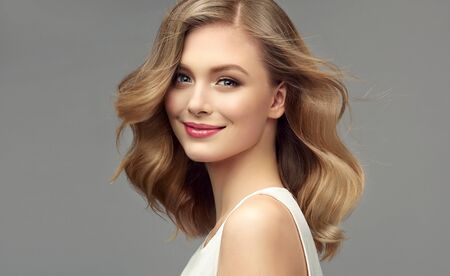 Foto de Model with dark blonde hair. Frizzy, elegant hairstyle is surrounding lovely face of tenderly smiling young woman. Hair care and hairdressing art. - Imagen libre de derechos