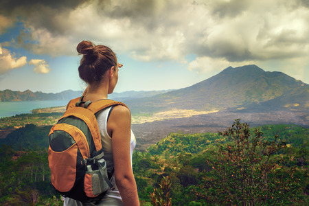 Foto de Lady tourist with a backpack standing on top of the mountain and enjoy the beautiful volcano - Imagen libre de derechos