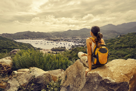 Foto per Woman traveler looks at the edge of the cliff on the  sea bay of mountains - Immagine Royalty Free