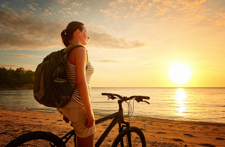 Photo pour Young woman with backpack standing on the shore near his bike and looking on sunset. Traveling along Asia, active lifestyle concept - image libre de droit
