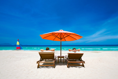 Photo pour Couple on a tropical beach relax in the sun on deck chairs under a red umbrella.  Travel  background . - image libre de droit