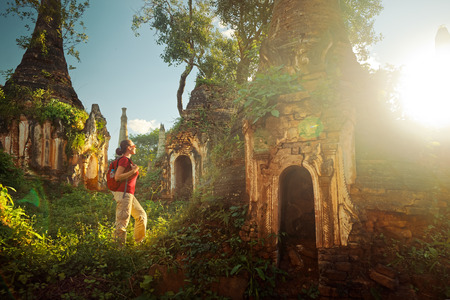 Foto de Backpacker traveling with backpack and looks at sunset ancient Buddhist stupa of the temple complex In Dein, Inle Lake. MayanmarTraveling along Birma, freedom and active lifestyle concept - Imagen libre de derechos
