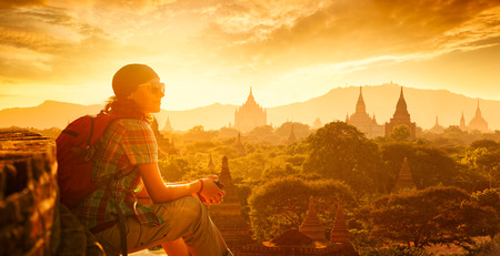 Foto de Young traveller enjoying a looking at sunset on Bagan, Myanmar Asia.  Traveling along Asia, active lifestyle concept - Imagen libre de derechos