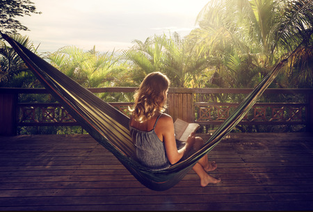 Photo for Young woman reading a book in a hammock on the terrace in the jungle at sunset - Royalty Free Image
