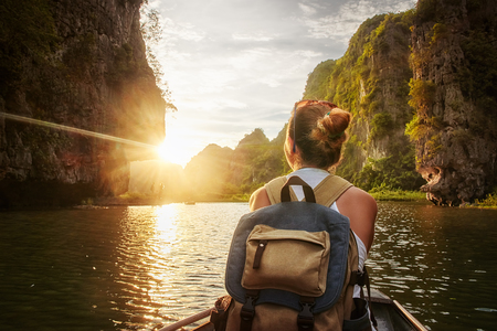 Foto de Happy woman with backpack traveling by boat enjoying sunset among of karst mountains in the North of Vietnam. Travel and active lifestyle, summer holiday concept. - Imagen libre de derechos