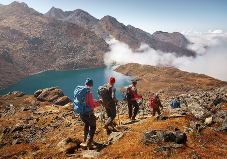 Foto de Group of tourists with backpacks descends down mountain trail to lake during a hike in the national park Lantang, Nepal. Beautiful inspirational landscape, trekking and activity. - Imagen libre de derechos