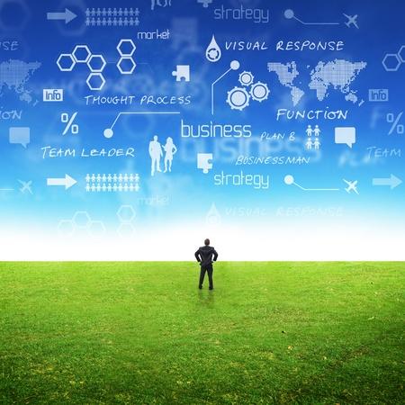 Foto de A businessman in a field with ideas in the sky. Conceptual - Imagen libre de derechos