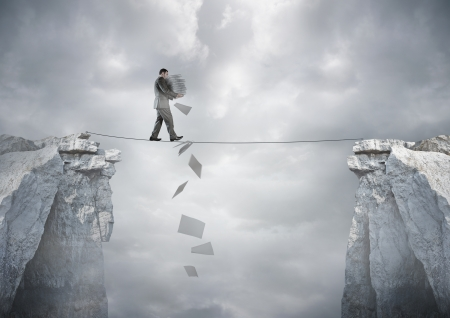 Foto de Business Balance - A businessman carrying paperwork walking over a tight rope. - Imagen libre de derechos